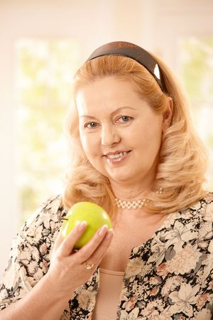 Portrait of senior blonde woman holding green apple smiling at camera in closeup. Stock Photo - 6746155