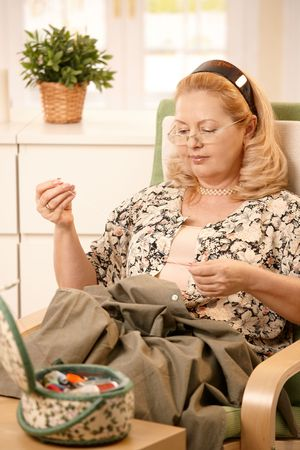 Senior woman sitting in armchair sewing a shirt, using sewing kit. Stock Photo - 7136641