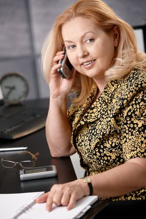 Senior smiling blonde businesswoman talking on mobile phone checking calendar sitting in office. photo