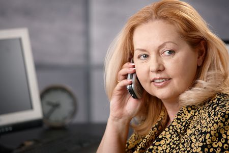 Closeup portrait of senior blonde businesswoman talking on mobile phone in office. photo