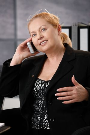 Closeup portrait of senior female executive sitting in office, listening to phone call. photo