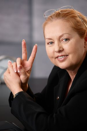 wise woman: Closeup portrait of successful senior businesswoman smiling, showing sign of victory, looking confident. Stock Photo