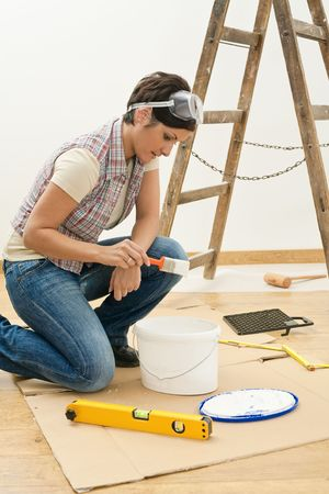 Young woman holding paint brush, working at flat renovation. photo