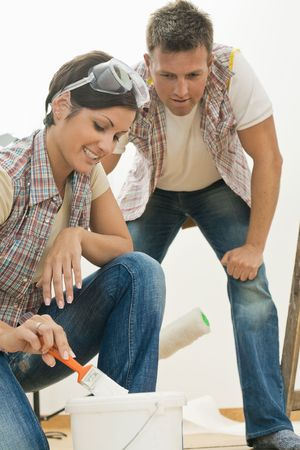 Smiling woman using paint brush, handsome man looking at her dipping brush into bucket. photo