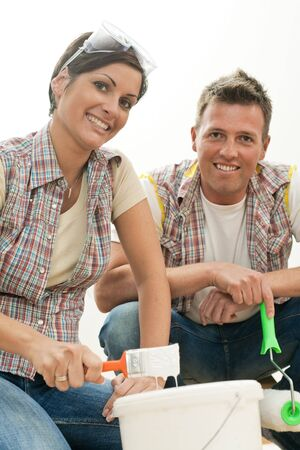 Happy couple working on painting walls together holding paint brush, smiling. photo