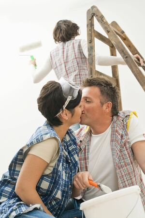 Couple kissing at home renovation, holding paint brush, female friend standing on ladder painting wall with paint roller.  photo