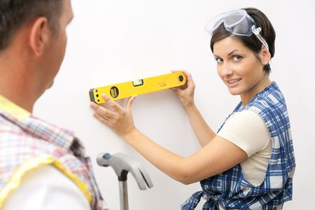 Smiling woman in focus holding spirit level, looking at camera, man holding hammer. Stock Photo - 6746098