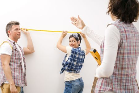 Couple holding measuring stick at wall looking at woman standing on ladder holding spirit level directing to right place.  photo