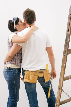 Couple standing embracing each other, woman kissing man on cheek, man wearing tool kit holding hammer looking at white wall, woman holding paint brush. photo