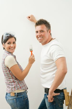 Happy couple working on improving home, painting wall, woman holding paint brush, looking at camera, smiling. photo