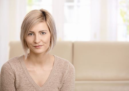 one adult only: Portrait of attractive young blond woman at home looking at camera, smiling. Copy space for text. Stock Photo