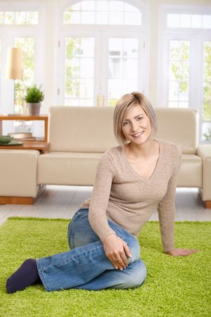 Portrait of attractive young blond woman sitting on floor at home looking at camera, smiling. Copy space above. Stock Photo - 7136691