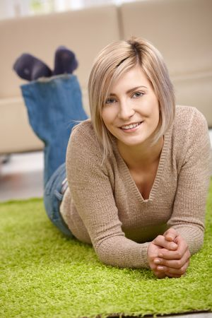 Portrait of attractive blond woman lying on floor at home, looking at camera, smiling. Stock Photo - 6746176
