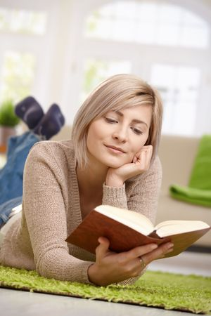 Young blonde woman relaxing on floor at home reading book. Copyspace above. photo