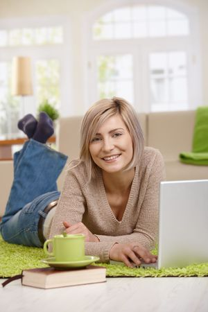 Attractive young blonde woman lying on floor at home in living room browsing internet on laptop computer, smiling. Stock Photo - 7136700