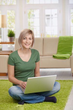 Feliz mujer sentada en suelo en casa, en la sala de estar con el equipo portátil, mirando la cámara.