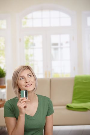 Woman sitting at home with credit card in hand dreaming about shopping. Copyspace above. photo