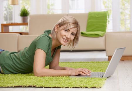 Happy blond woman lying on floor in living room browsing internet with laptop computer. photo