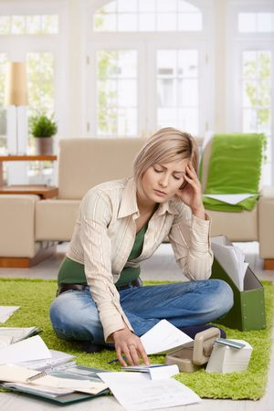 reviewing documents: Troubled woman sitting on floor with crossed legs, doing calculation in living room. Stock Photo
