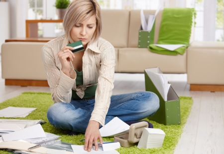 calculations: Worried woman checking documents, holding credit card, sitting on floor with crossed legs at home. Stock Photo