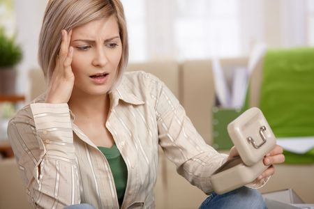 Worried woman sitting at home, looking at money box in shock. Stock Photo - 6746170