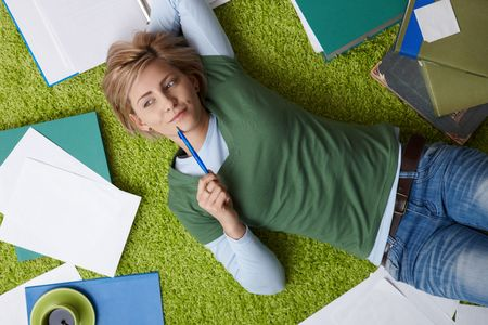 Attractive young woman thinking on floor, looking aside, pen in hand, surrounded by books and notes. photo