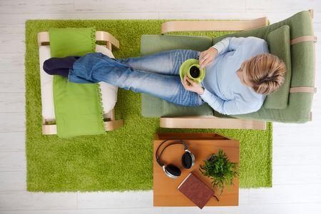 ハイアングルビュー: 女性は足を組んでハイアングルでフットボードに肘掛け椅子に座ってコーヒーを持っています。