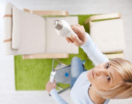 Mujer en la vista de ángulo alto intentando cambiar la pie de bombilla en la escalera en la sala de estar buscando up.Focus colocado en la bombilla. Foto de archivo