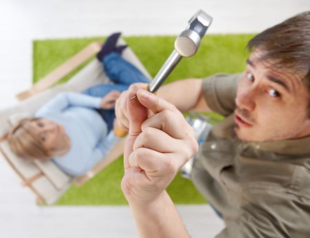 In overhead view man trying to nail with hammer standing on ladder, hand with nail in focus, woman in background looking up from armchair. photo