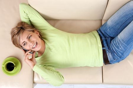 Laughing woman talking on cellphone lying on couch, with coffee mug at hand, in overhead view. photo