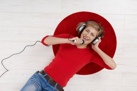 Woman lying on round red carpet of living room floor with headphones holding microphone, singing in high angle view. photo