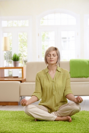 Woman sitting on floor at home doing yoga meditation. Stock Photo