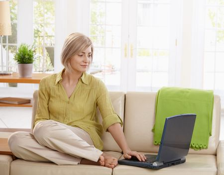 Attractive woman sitting on living room couch looking at laptop computer.  photo