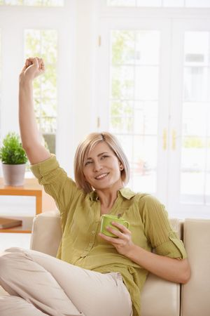 Portrait of young woman sitting on couch at home, drinking tea, stretching and smiling. photo
