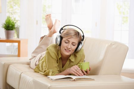 Woman drinking coffee, lying on couch reading book, wearing headphones at home. photo