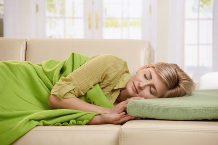 lay: Blond woman sleeping with blanket on couch in sunlit living room at home. Stock Photo
