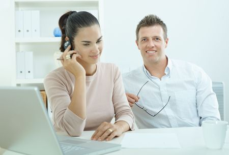 outworking: Couple working on laptop computer at home office, happy, smiling. Woman calling on mobile phone. Stock Photo