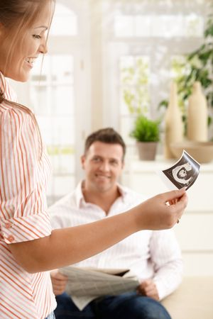 Smiling woman looking at baby's ultrasound picture held in hand, man smiling in background at home. Stock Photo - 7136708