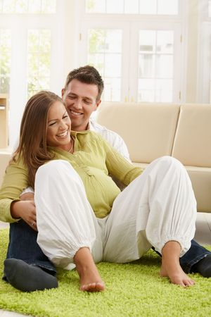Laughing couple expecting baby doing pregnancy exercise on living room's floor. Stock Photo - 7136715
