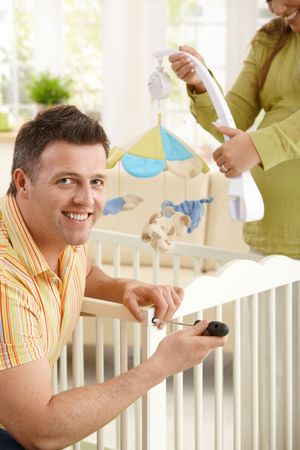 Portrait of man fixing baby bed, smiling at camera, smiling expectant woman holding baby toys in background. Stock Photo - 7136710