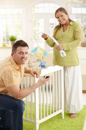 Portrait of happy couple smiling at camera, fixing bed for baby together at home. Stock Photo - 7136711