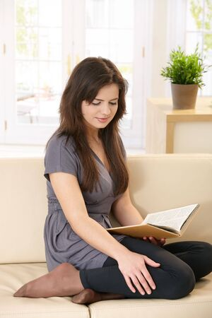 Pretty girl sitting on couch, reading book with legs pulled up, smiling. photo