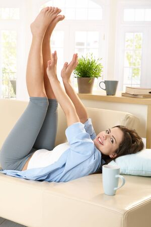 Cheerful girl looking at camera, lying on sunlit living room couch, stretching arms and legs. photo