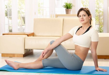 Pretty girl sitting on sport mat in front of sofa, stretching, looking at camera. photo