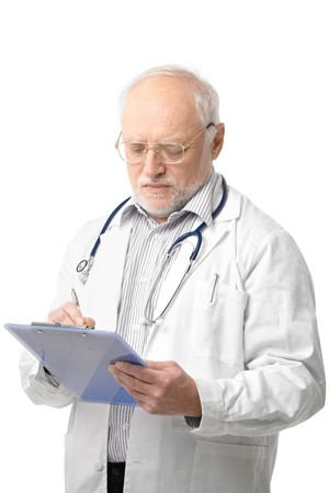only: Serious senior doctor looking down at clipboard doing paperwork. Isolated on white background.