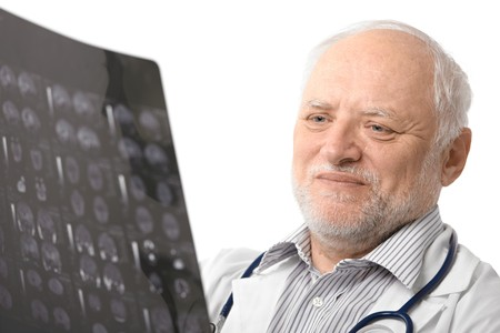 Portrait of happy senior doctor looking at X-ray image, smiling. Isolated on white background. photo