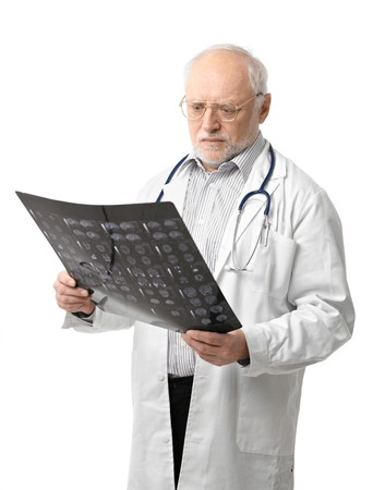 unsmiling: Portrait of serious senior doctor looking at X-ray image. Isolated on white background.