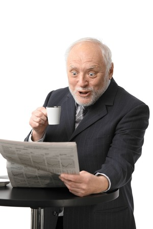 Portrait of surprised senior businessman drinking coffee reading newspaper, isolated on white. photo