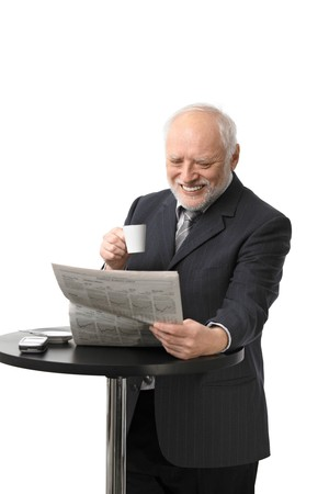 Portrait of happy senior businessman drinking coffee reading newspaper, laughing, white background. photo