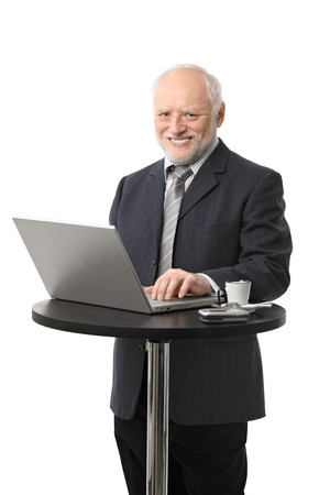 Portrait of happy senior businessman using laptop on coffee table, laughing, cutout. photo